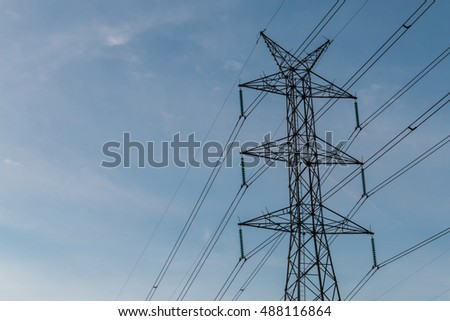 High voltage pole with a blue sky background.