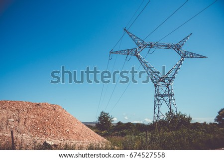 High voltage pole with stretched electric cables over a dirt mound