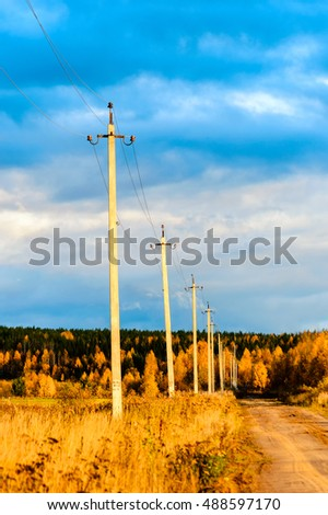 high voltage poles along the road an autumn day