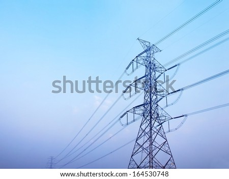 High voltage post against clear blue sky - stock photo