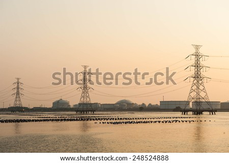 high voltage post.High-voltage tower over oil and gas tanker background. - stock photo