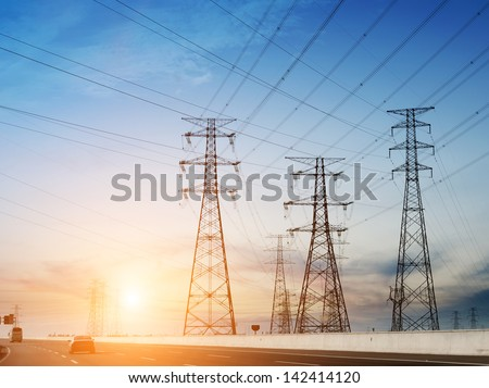 high voltage post.High-voltage tower sky background,besides the highway. - stock photo
