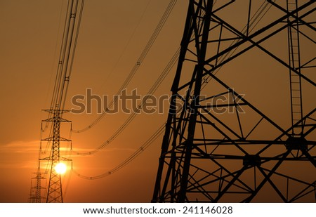 High voltage post on sunset light - stock photo