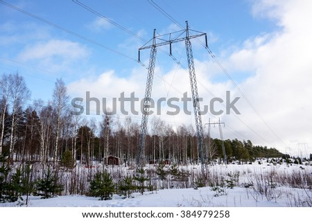 High voltage post or High voltage tower. Electricity transmission pylon with cloudy sky in winter. Finland - stock photo