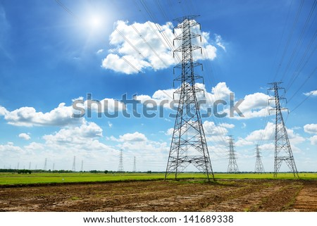 High voltage post or High voltage tower in green field - stock photo