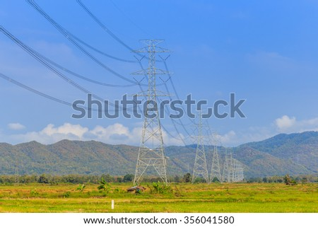 high voltage post or high voltage towers and power lines with blue sky - stock photo