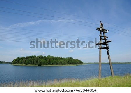 high-voltage power line against the background of the blue sky along the coast of the lake