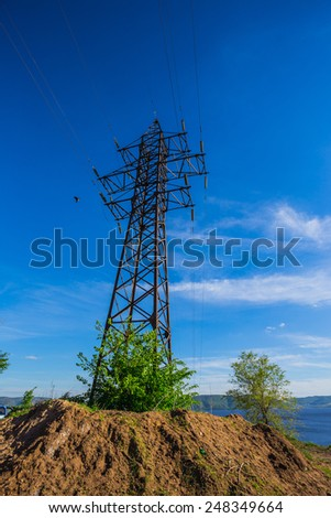 High-voltage power line on the shore of the river - stock photo