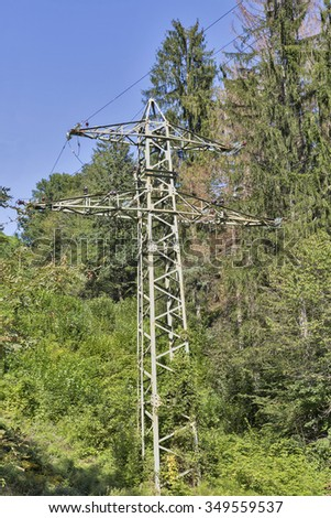 high voltage power line tower in the mountain forest with clear sky