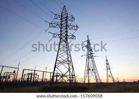 High voltage power lines at twilight at the horizon - stock photo