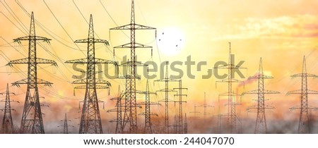 High-voltage power lines in an industrial area .Against the background of a frosty foggy morning. - stock photo