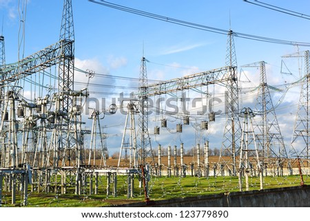High voltage power lines with blue sky and clouds
