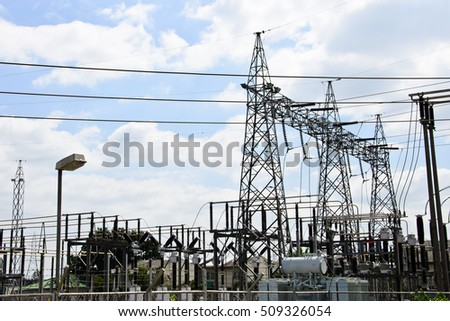 High voltage power lines with electricity pylons at blue sky.
