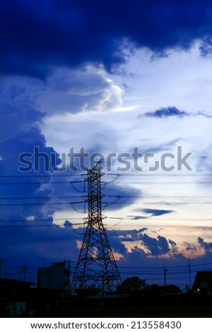 High voltage power lines with electricity pylons at twilight. - stock photo