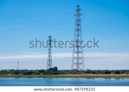 High-voltage  power lines with two towers on the river bank