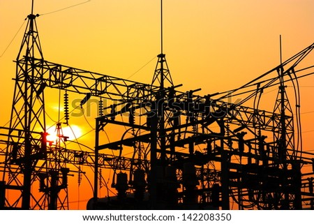 High voltage power plant and transformation station at sunset - stock photo