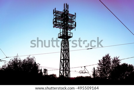High voltage power pylons against blue sky with clouds and green forest on sunset. silhouette of high voltage power towers against blue sky with clouds and green forest on sunset