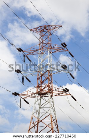High voltage power pylons Behind a cloud covered sky. - stock photo
