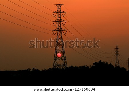 High voltage power pylons in sunset scene twilight - stock photo