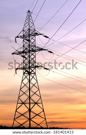 High-voltage power supply line metal tower silhouette on beautiful sunset vertical view