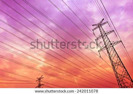 High voltage power tower pylon and line cables against orange sky - stock photo