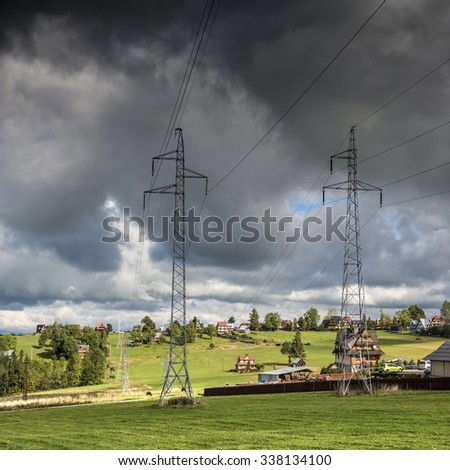 High-voltage power transmission towers in cloudy stormy sky background - stock photo