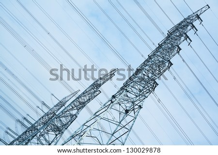 High-voltage power transmission towers in sky background - stock photo
