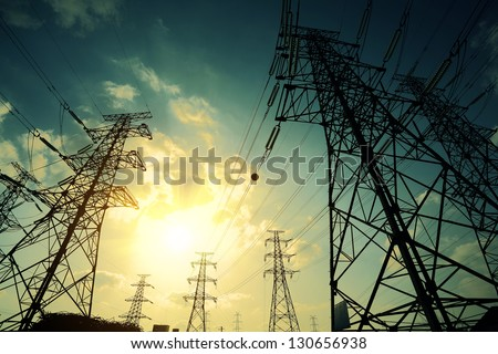 High-voltage power transmission towers in sunset sky background - stock photo