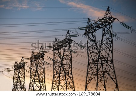 high voltage pylons silhouette cloudy sky background - stock photo