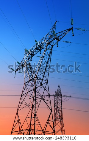 high voltage pylons silhouettes evening background - stock photo