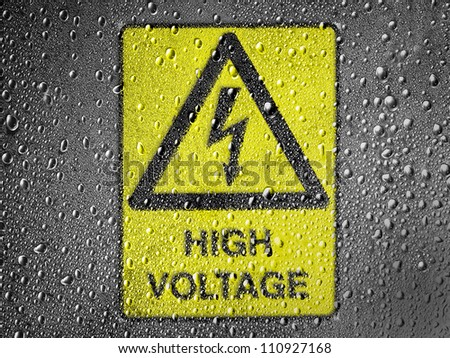 High voltage sign drawn at metal surface covered with rain drops - stock photo