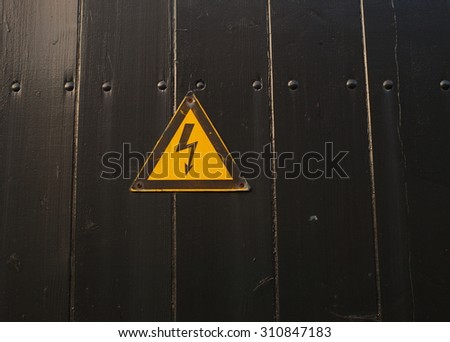 high voltage sign on black painted wood