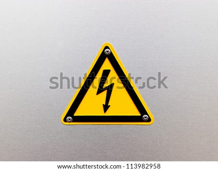 High voltage sign on the metal background