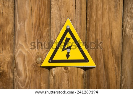 High voltage sign on wood background