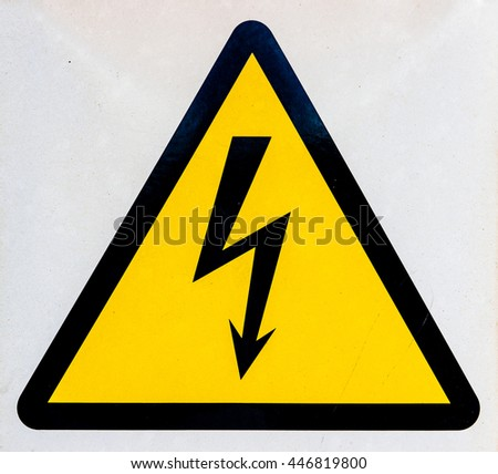 High voltage sign (symbol), black triangle and flash (bolt) on the yellow background. Some dust and scratches visible. - stock photo