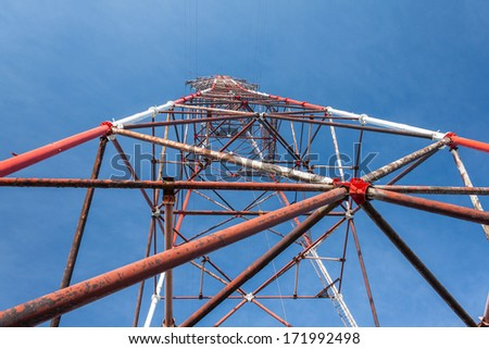 High-voltage tower against blue sky background.