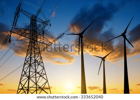 High voltage tower and wind turbines against the sunset - stock photo