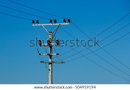 High voltage tower (electricity post), blue sky, crossing wires.