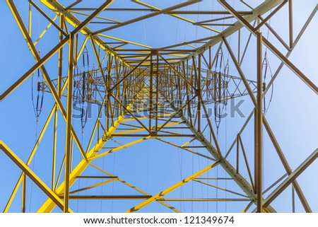 high voltage tower in rural landscape with blue sky