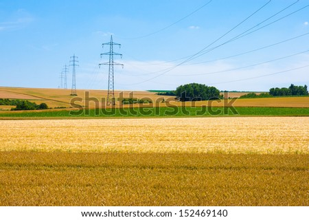 High-voltage towers and cables in agricultural fields on a blue sky background. - stock photo