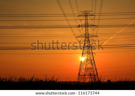High voltage towers at sunset - stock photo