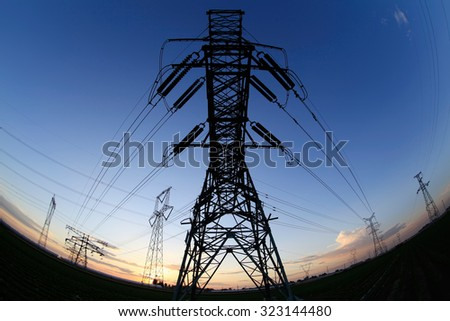 High voltage towers under the setting sun, close-up