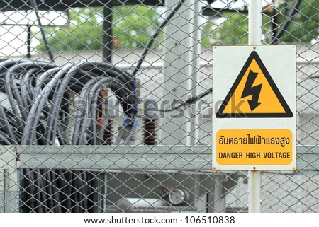High voltage transformer substation behind barbed wire chain link fence with Danger High Voltage sign. - stock photo