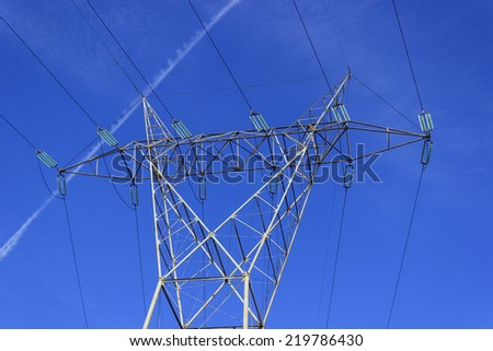 High voltage transmission line pylon with airplane mark behind.