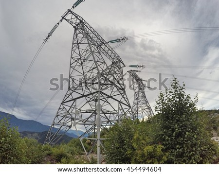 High voltage transmission power line towers on a mountain top, cloudy skies - stock photo