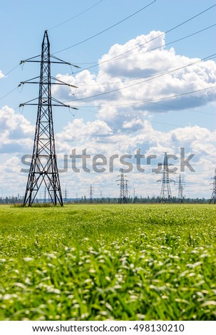High voltage transmission tower lines on countryside in summer day