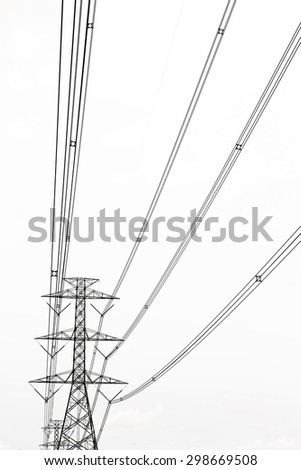 High voltage transmission tower with gray clouds background. - stock photo