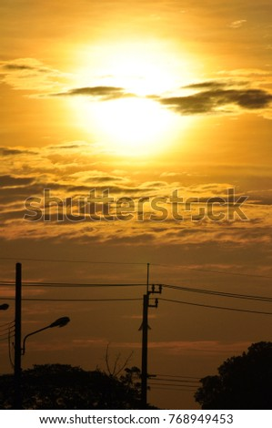 high voltage transmission towers with golden yellow light during sunrise. Sunset and high voltage transmission towers.The golden sky