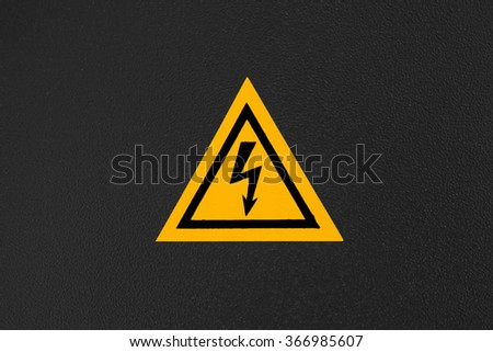 High voltage triangle warning sign mounted on black metal wall