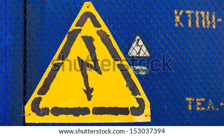 High voltage yellow sign mounted on blue metal rabitz grid with blue metal wall on background - stock photo